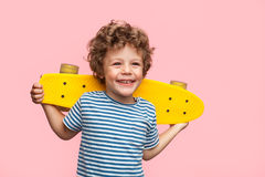 Cheerful boy with longboard on pink. Little curly boy holding yellow longboard and looking away on pink background Royalty Free Stock Photography