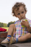 Little curly boy with juice in hands. Little curly boy in the checked shirt with juice in hands on a background blue sky in the country Royalty Free Stock Image
