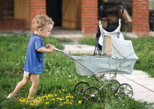 Little curly boy pushes a baby-carriage. A little curly boy pushes before itself a baby-carriage in a court rural house on a background yellow plants and brick Stock Photos