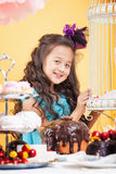 Little curly brunette posing with sweets Stock Photos