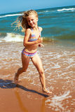 Little curly cheerful girl runs along the shore of the ocean on Stock Image
