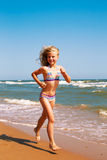 Little curly cheerful girl runs along the shore of the ocean Royalty Free Stock Image