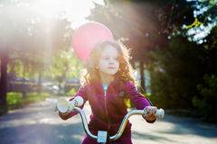 Little curly girl on bicycle in the park, soft focus in sun rays. Stock Photo