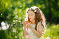 Little curly girl blowing dandelion. stock images