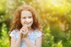 Little curly girl blowing dandelion. Royalty Free Stock Image