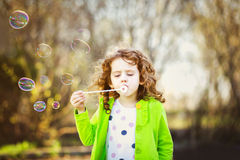 A little curly girl blowing soap bubbles. Stock Photos