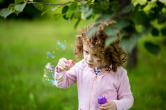A little curly girl blowing soap bubbles Stock Photo
