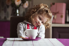 Little curly girl with cup sitting at the table Stock Photo