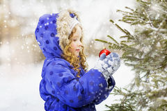 Little curly girl decorates the Christmas tree. Royalty Free Stock Photos