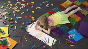 Little curly girl drawing with color pencils on the floor at home, childhood. Stock footage stock video footage