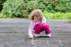 Little curly girl draws on asphalt Stock Image