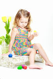 Little curly girl with Easter eggs Stock Photos