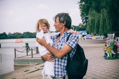 A little curly girl and her father outdoors. royalty free stock images