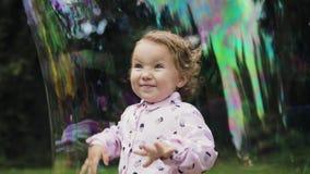 Little curly girl in huge bubble feeling happy. Slow motion. Bubble show. Little curly girl in huge bubble feeling happy. Slow motion. Bubble show stock video
