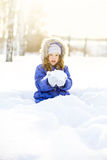 Little curly girl near fir tree branch in snow for new year. Royalty Free Stock Photo