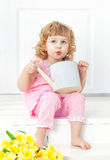 Little curly girl in pink dress and barefoot sits on a white porch and playing with children's watering can. Stock Image