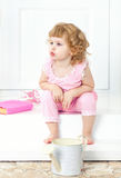 Little curly girl in a pink dress sits with a thoughtful look and watch into the distance, on a white porch. stock images