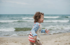 Little curly girl playing in the sand on seashore Stock Image