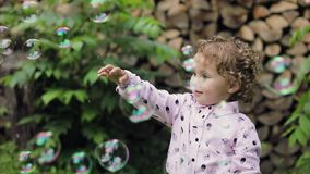 Little curly girl playing with soap bubbles feeling happy. Slow motion. Bubble show. Little curly girl playing with soap bubbles feeling happy. Slow motion stock video footage