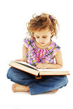 A little curly girl reading a book on the floor Stock Image