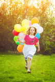 Little curly girl running with colored balloons. Happy childhood Royalty Free Stock Image