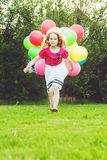 Little curly girl running with colored balloons. Happy childhood Royalty Free Stock Images
