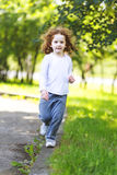 Little curly girl runs in the spring park. Stock Images