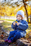 Little curly girl sits in autumn park Stock Images