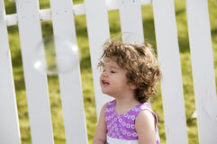 Little curly girl with soap bubbles Royalty Free Stock Images