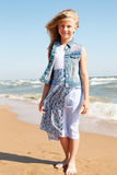 Little curly girl stands on the shore of the ocean. Stock Photography