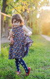 Little curly girl with a teddy bear in his hands. Little girl in a spring garden with a toy Royalty Free Stock Photos