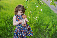 Little curly girl with a teddy bear in his hands. Little girl in a spring garden with a toy Royalty Free Stock Photo