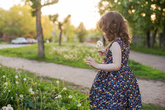 Little curly girl with a teddy bear in his hands. Little girl in a spring garden with a toy Stock Photo