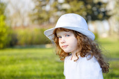 Little curly girl in a white hat. Royalty Free Stock Photos