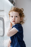 The little curly girl in window Royalty Free Stock Image
