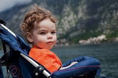 Little curly-haired boy sitting in the pram on the seafront. Little curly-haired boy sitting in the pram on the beach and looks into the distance Stock Images