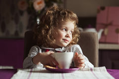 Little curly-haired girl with a cup Royalty Free Stock Photos