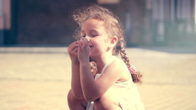 A little curly-haired girl laughing at the little sea shell and playing with it. A charming girl traveling with her stock video