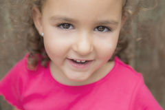 Little curly haired girl looking at camera Stock Photos
