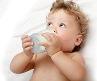 Little curly-headed baby sucks a bottle Stock Photography