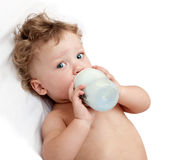 Little curly-headed baby sucks a bottle Stock Images