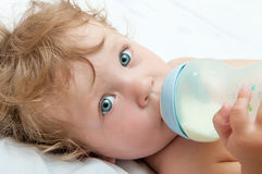 Little curly-headed baby sucks a bottle Royalty Free Stock Image