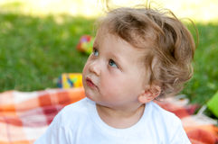 Little curly-headed boy looks to the left Stock Photography