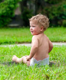 Little curly-headed child is sitting on the green grass Stock Images
