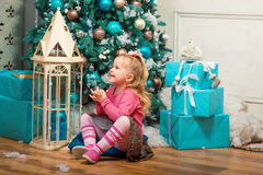 Little curly smiling girl sitting nearly Christmas tree Stock Photo