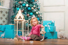 Little curly smiling girl sitting nearly Christmas tree Stock Image