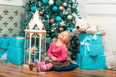 Little curly smiling girl sitting nearly Christmas tree Stock Photography