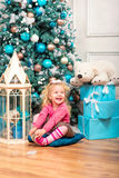 Little curly smiling girl sitting nearly Christmas tree Royalty Free Stock Photos