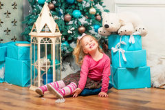 Little curly smiling girl standing nearly Christmas tree Royalty Free Stock Photo