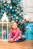 Little curly smiling girl standing nearly Christmas tree Stock Image
